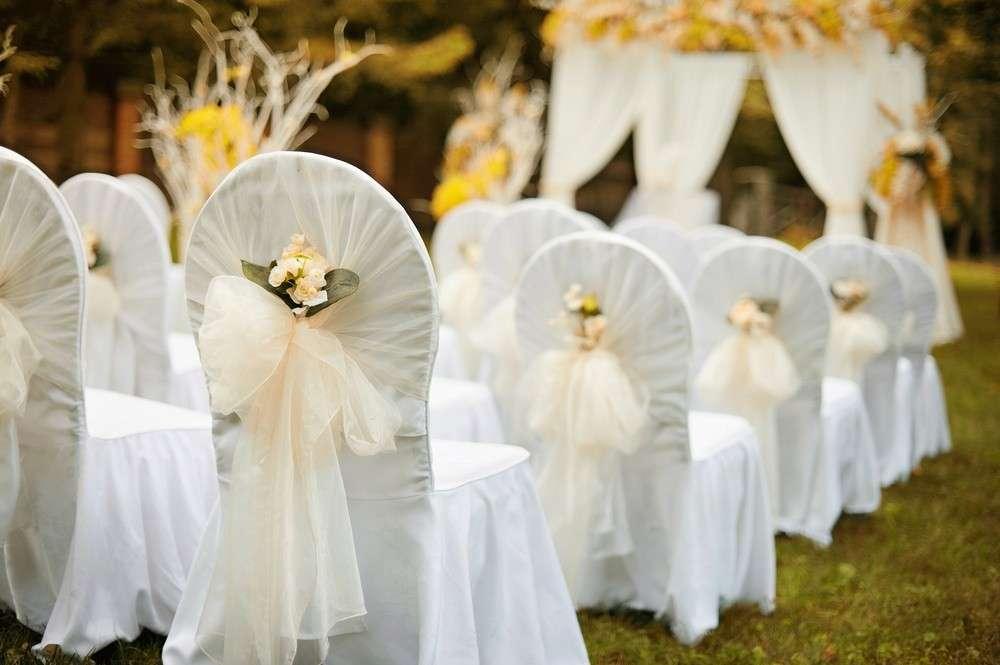 Auch Stuhlhussen mit hübschen Bändern verleihen dem Hochzeitsraum eine zusätzliche festliche Atmosphäre
