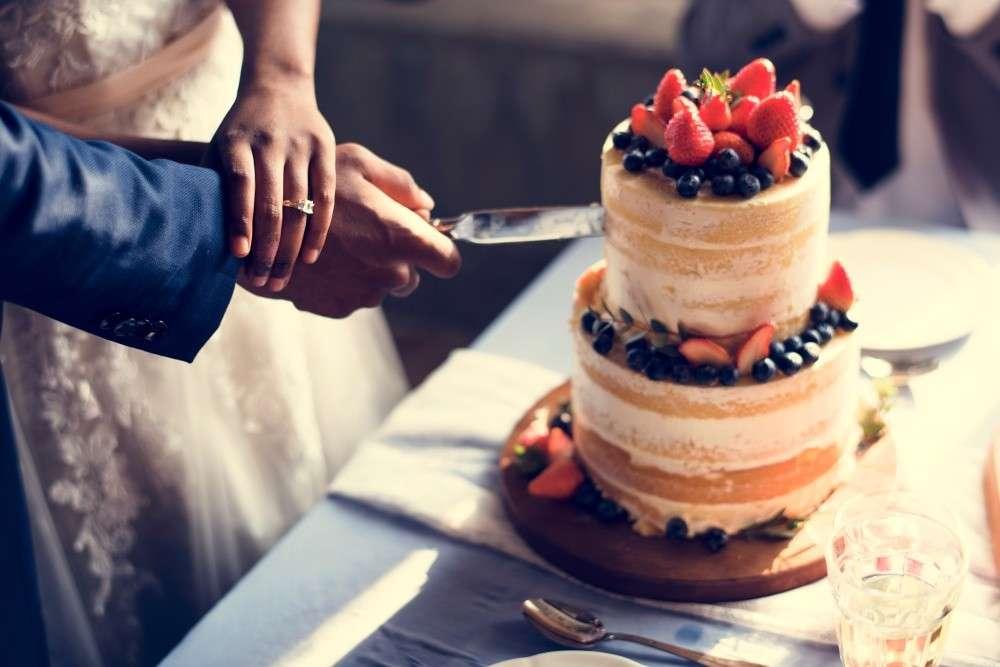 Gemeinsames Anschneiden der Hochzeitstorte während der Hochzeitsfeier
