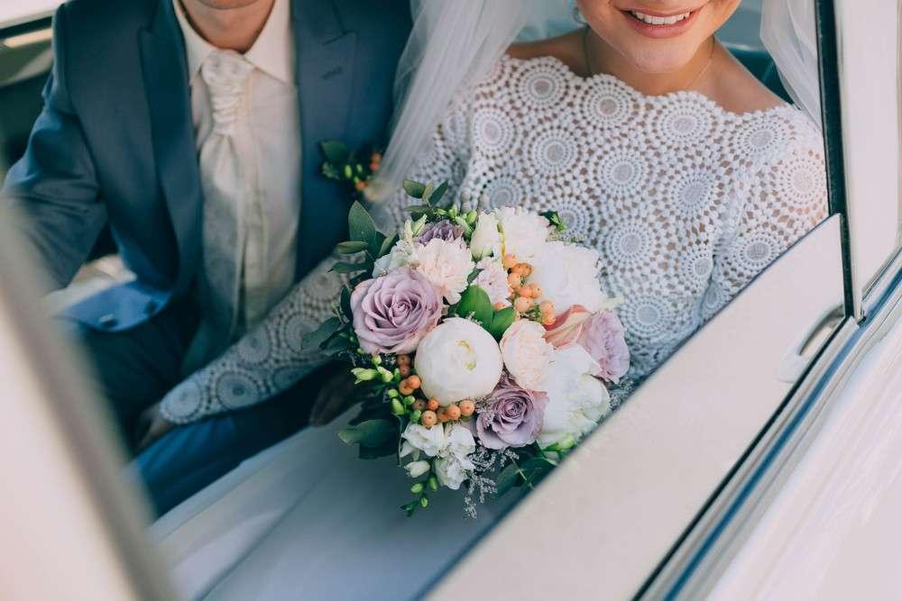 Schöne Braut in einem weißen Kleid und Bräutigam in Tuxedo sitzen in einem Auto und halten eine Hochzeitsbukett